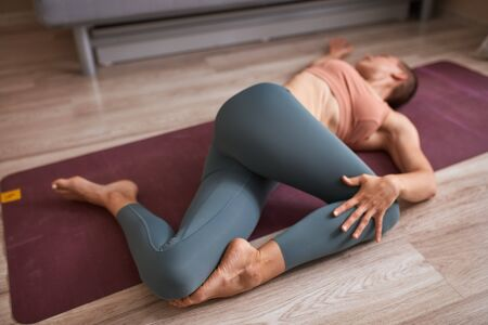 Female Caucasian female do yoga exercise at home on mat, ltying on floor. body muscles, close up image, floor background