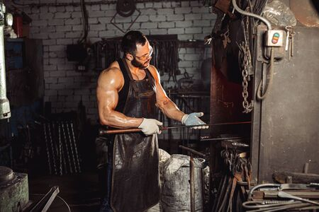 side view on careful forger man holding metal for future manufacturing, studying it, wearing leather apron and protective eyeglasses and gloves. isolated in workshop