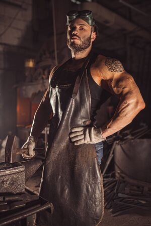 Portrait of serious confident strong young metalworker in black apron stand looking at camera, work in workshop