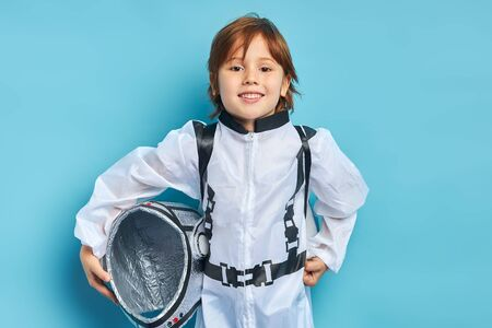 Portrait of cute caucasian boy wearing white protective suit and holding helmet stand isolated over blue background. look at camera