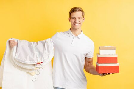 express delivery by young vigorous smiling man in white t-shirt isolated over yellow background. courier, delivery service concept Stock Photo
