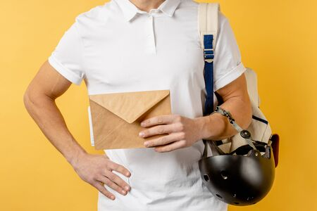 cropped young postman holding letter in hands, wearing white t-shirt and helmet from bike. delivery concept. yellow background