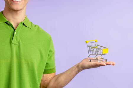 portrait of cropped young man in green t-shirt holding small toy truck for shopping from hypermarket, isolated over purple background