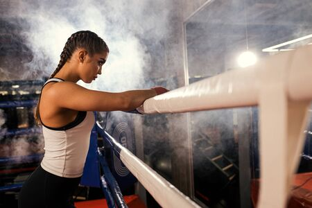 Side view on boxer female with bowed head down isolated over smoky ring, lean on fence. Brunette woman in sportive wear keen on kickboxing Stock Photo