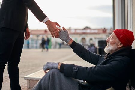 Senior bedelaar zit naast straat met verzoek om hulp bij het ontvangen van wat munten van een vriendelijke zakenman. Man steekt hand uit naar daklozen.