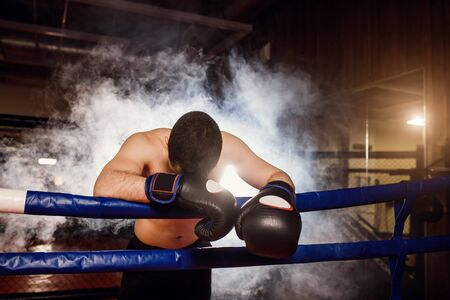 exhausted tired man with bowed head down on fence in ring, wearing black boxing gloves, in smoky space