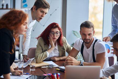 Giovane gruppo di uomini d'affari coinvolti in attività creative che discutono di lavoro in ufficio e si siedono sotto shock mentre guardano lo schermo del laptop, lo sfondo dell'ufficio