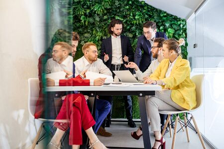 young and successful business people, co-workers having beneficial meeting in modern office with beautiful interior