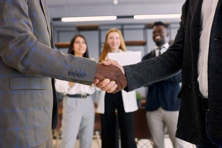 multi-ethnic team after successful meeting shake hands to each other. African anc caucasian executives in tuxedo in office