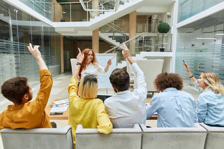 Serious strict coach with long wavy hair, raises hand, holds pencil, looks up with dissatisfied expression not paying attention to group of creative designers Banco de Imagens