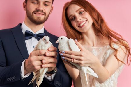 Beautiful caucasian couple after marriage proposal stand holding doves in hands, isolated over pink background