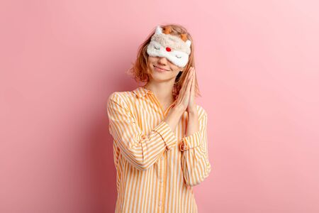 portrait of smiling girl with short hair, wearing pajamas and blindfold, want to sleep, she doesn't get enough sleep at morning, isolated pink background