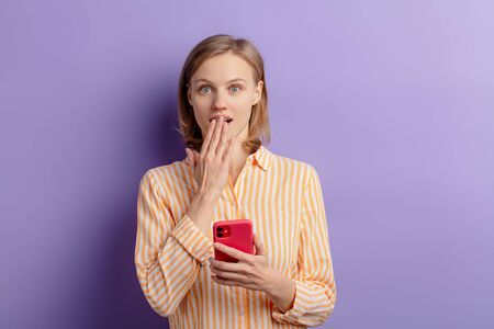portrait of beautiful shocked, surprised woman after receiving message from friend, holding smartphone in hands and look at camera, closed mouth with hand. isolated purple background