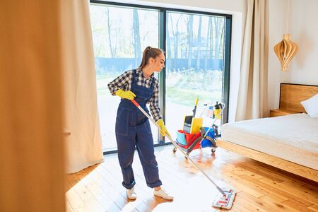 Young caucasian girl in blue uniform from cleaning service holding mop for washing floor, clean up bedroom