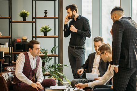 young caucasian business leaders gathered in office for coworking, hold meeting for discussion and having effective cooperation, everyone dressed in formal clothes Stok Fotoğraf