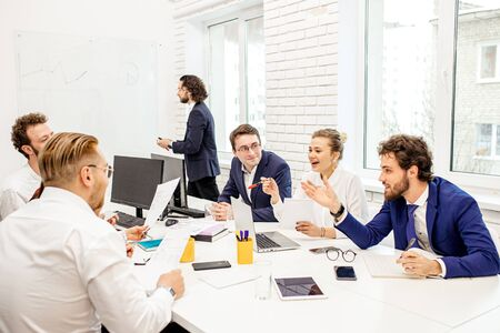 group of young caucasian business leaders gathered in office to discuss projects and ideas together, colleagues sit on table and have friendly conversation, smiling. Business people concept