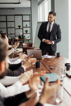 business coach, leader man give speech to co-workers sitting at table in office. pleasant bearded man in tuxedo stand representing his project in modern boardroom,. business people concept Banco de Imagens