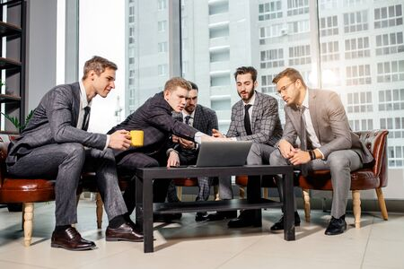 young business guys in formalwear, in tuxedo work in office together, using laptop, discuss business strategies, ideas and projects Banco de Imagens