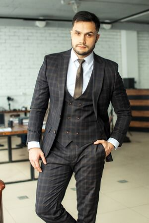 confidently looking bearded man wearing formal clothes in modern boardroom after business conference with partners. success and business people concept