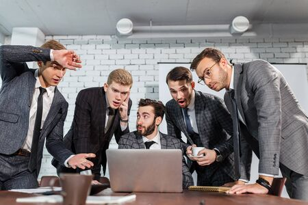 coworking business team stay in shock at work, look at laptop, discuss business strategies and planning work, everyone in tuxedo