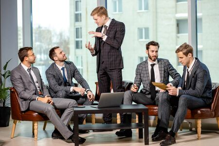 business team brainstorming in modern executive office, group of men in elegant suits. business coworking concept. people gathered to discuss business strategies
