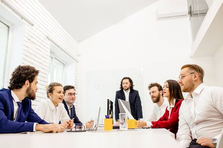 caucasian boss in tuxedo and employee, business people gathered in office for discussion, sharing experience and solving problems inside the company