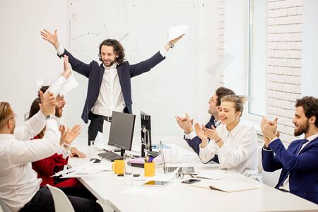 young caucasian boss in tux raised hands from happiness, look at co-workers and smile, cogratulate and celebrate, isolated in business office