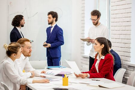 young diverse caucasian people hold business meeting in office, everyone in formal wear, have conversation and discussion of business project and deadlines