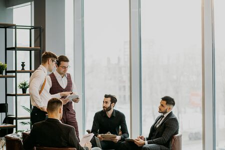 coworking of handsome guys in tuxedo, isolated in modern office. teamwork of successful people gathered to develop business project and have conversation, discussion Banco de Imagens