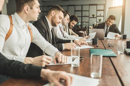 young caucasian business people in formal wear sit in boardroom coworking, making notes, using papers. discuss and write business ideas Reklamní fotografie - 138201662