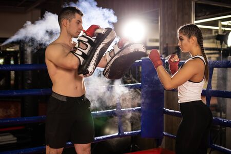 Experienced boxer man train young woman to fight in ring, wearing sportive wear and protective red bandages on hands