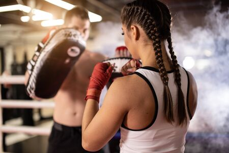 young sportive fit couple training together in ring, man with naked torso and woman in sportive wear, wearing red protective bandages on hands. Boxing, sport concept. Smoky space Stock Photo