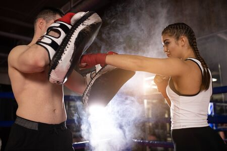 Fit muscular caucasian man and woman training together, boxing dressed in sportive wear. Healthy lifestyle, sport, boxing concept