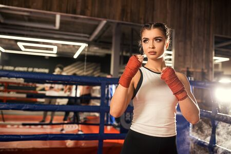 Portrait of strong muscular fitness woman ready to fight in gym, wearing red bandage on hands and sportive wear