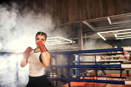 young and beautiful caucasian female in sportive wear training in ring, have fit muscular body, ready to fight in combat readiness. Sport, fitness, boxing concept