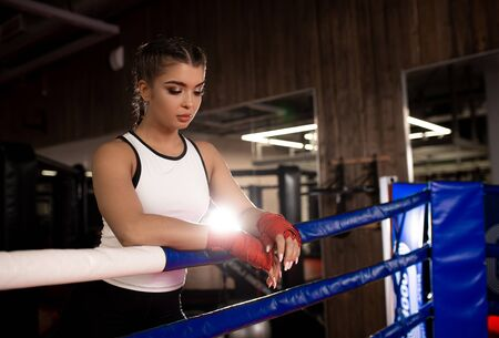 tired muscular boxer female after intense effective training in gym, wearing sportive wear, red protective bandages Standard-Bild - 139187286
