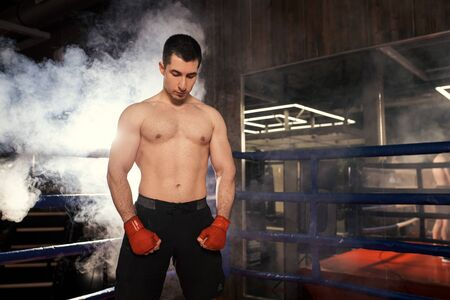 Boxer man with muscular body stand isolated over smoky space, after fight in ring, wearing protective boxing gloves. Healthy lifestyle, sport concept