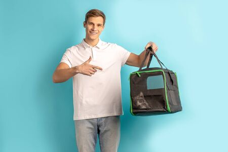 portrait of young caucasian delivery man in unifrom carrying things for customer, isolated over blue background. express delivery concept