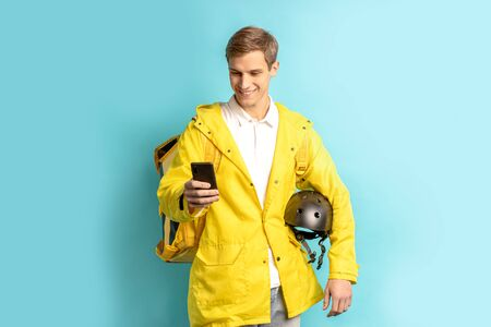 portrait of young smiling caucasian man working in express delivery service, driving motorcycle, holding helmet and wearing yellow uniform look at smartphone isolated over blue background