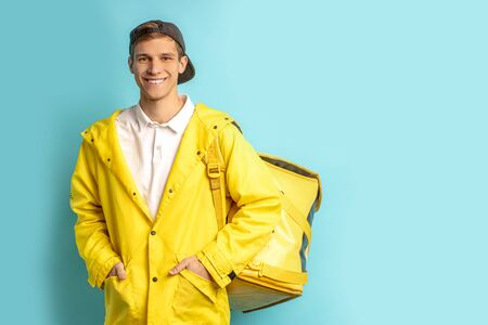 portrait of nice deliverman in yellow uniform isolated over blue background, wearing cap and carrying backpack with orders, look at camera and smile Reklamní fotografie - 138201996