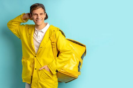 portrait of good-looking deliverman in special yellow uniform, carrying orders in backpack for customers and looking at camera isolated over blue background