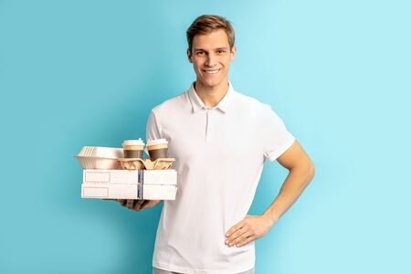 portrait of handsome positive young caucasian man holding boxes with food, wearing white t-shirt, smile and look at camera isolated over blue background. delivery service concept Reklamní fotografie - 138202634
