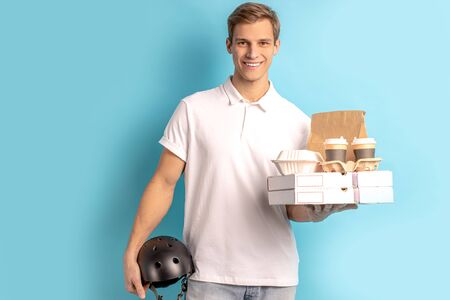 portrait of handsome young caucasian guy holding boxes with food and helmet for motorcycle, wearing white t-shirt, smile and look at camera isolated over blue background. delivery service concept Banco de Imagens