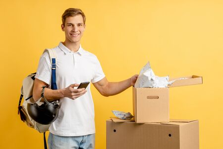 young caucasian man courier with boxes and smartphone isolated over yellow background, postman with unpacked boxes, express delivery concept Reklamní fotografie - 138202047