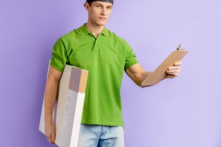 portrait of young caucasian delivery man in green t-shirt, handsome pizzaman holding box with pizza and list of ordered pizza sets. courier, delivery concept Reklamní fotografie - 138201640