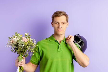 express delivery by young caucasian male holding beautiful flowers in hands and looking at camera. handsome man in green t-shirt work as courier in bike, happy to deliver isolated over purple Banco de Imagens