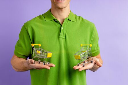 portrait of cropped man with toy trucks isolated over purple background, green t-shirt on shopper man. shop lover