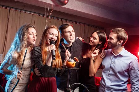 holiday, party,celebration concept. young people have cheerful pastime in karaoke, positive people together sing in microphone and have fun, chilling out