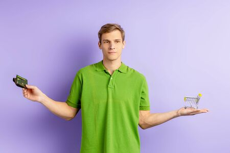 uncertain young caucasian man holding toy truck and wallet in hands, wearing green t-shirt and looking side, can not choose