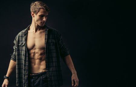 young caucasian man with muscular strong body opened torso, checkered casual shirt on him, he looks side isolated over black background Banco de Imagens